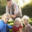 Young family sit together in garden — Stockfoto