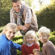 Young family sit together in garden — Stock Photo