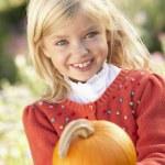 Young girl posing with pumpkin in garden — Stock Photo #11879013