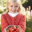 Young girl posing with tomatoes in garden — Stock Photo