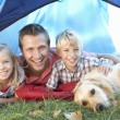 Stock Photo: Young father poses with children in tent