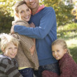 Young family pose in park — Stock Photo #11879057