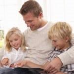 男人和孩子们一起读 — 图库照片