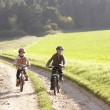 Two young children ride bicycles in park — Stock Photo #11879244