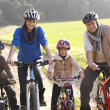 Young family pose with bikes in park — Stock Photo