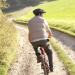 Young man rides his bike in park — Stock Photo #11879275
