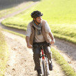 Young man rides his bike in park - Stock Photo