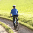 Young woman rides her bike in park - Stock Photo