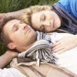 Young couple lying together on grass — Stock Photo #11879286
