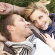 Stock Photo: Young couple lying together on grass
