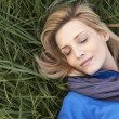 Young woman napping alone on grass — Stock Photo #11879299