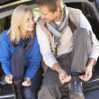 Young couple tie boots at rear of car — Stock Photo #11879315