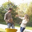 Young couple having fun with autumn leaves in garden — Stock Photo