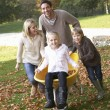 Family having fun with autumn leaves in garden — Stock Photo #11879325