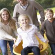Family having fun with autumn leaves in garden — Stockfoto