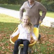 Father pushing child through autumn leaves on wheelbarrow - Photo
