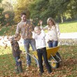 Stock Photo: Family throwing autumn leaves into the air in garden