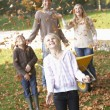Family throwing autumn leaves into the air in garden — Stock Photo #11879335