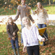 Family throwing autumn leaves into the air in garden — Stock Photo
