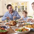 Happy family having roast chicken dinner at table - Photo