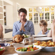 Family Saying Prayer Before Eating Roast Dinner - Foto de Stock