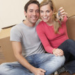 Royalty-Free Stock Photo: Young couple sit on the floor around boxes holding key in hand