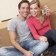 Young couple sit on the floor around boxes holding key in hand — Stock Photo