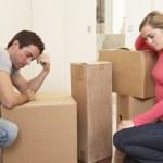 Young couple looking upset among boxes — Stock Photo