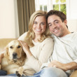 Young happy couple with dog sitting on sofa — Stock Photo #11879405