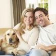 Young happy couple with dog sitting on sofa — Stock Photo