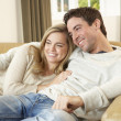 Young couple sitting and relaxing on sofa - Stock Photo
