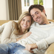 Young couple sitting and relaxing on sofa — Stock Photo #11879412