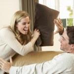 Young couple having fun laughing on sofa — Stock Photo