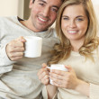 Young couple sitting and relaxing on sofa with cup in hand — Stock Photo