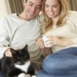 Young couple sitting with cat on sofa with cup in hand — Stock Photo #11879427