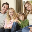 Happy young family sitting on sofa — Stock Photo