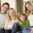Foto Stock: Happy young family sitting on sofa