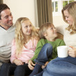Happy young family sitting and talking on sofa - 图库照片