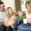 Happy young family sitting and talking on sofa — Stock Photo