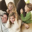 Happy young family having fun with pillows on sofa — Stock Photo