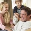 Young father with children having fun on sofa — Stock Photo #11879441
