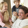 Young father with children having fun on sofa - Stock Photo
