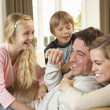 Happy young family playing together on sofa — Stock Photo