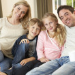Happy young family sitting on sofa holding cups — Stock Photo