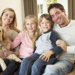 Happy young family sitting on sofa holding a dog - Lizenzfreies Foto