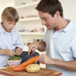 Stock Photo: Happy young mwith boy peeling vegetables in kitchen