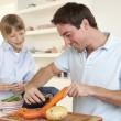Happy young man with boy peeling vegetables in kitchen — Stock Photo #11879488