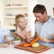 Happy family peeling vegetables in kitchen — Stock Photo