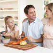 Happy family peeling vegetables in kitchen — Stock Photo #11879493