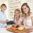 Young mother with children peeling vegetables in kitchen — Stock Photo